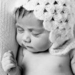 Newborn baby girl picture on white blanket.