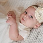 Beautiful baby girl dressed in her baptismal outfit.