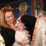 orthodox priest preforming baptism hair cutting