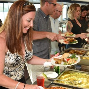 Event-goers smile as they pick from a buffet