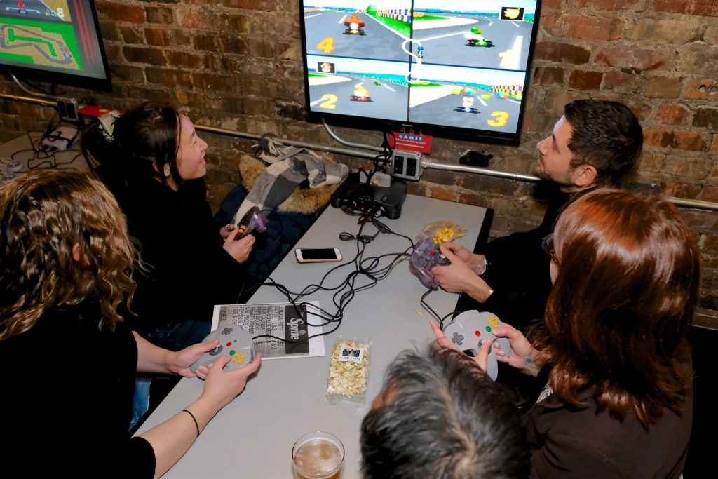 A group of young adults playing a video game and smiling at a restaurant
